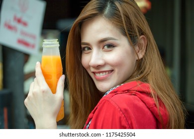 beautiful Young Asian women tourist traveler smiling with backpack drinking Orange juice in plastic bottles on the Traffic Road in China town Yaowarat city bangkok thailand .