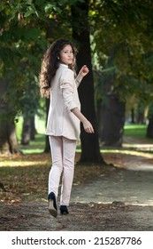 beautiful young asian-caucasian woman from behind with with long curly hair and head turn back walking on  alley in the park