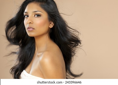 Beautiful young asian/indian woman with long hair posing on beige background