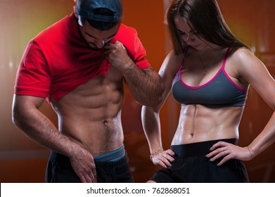 Beautiful young athletes man and woman demonstrate tight muscles in the gym