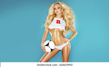 Beautiful young, athletic  blonde woman dressed in sports clothing, sitting on the ball and playing football and joyfully smiles
