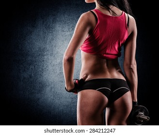 beautiful young athletic couple smiling and doing exercises with dumbbells