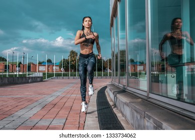 Beautiful young athletic girl tattoos runs morning for jog fitness training, sportswear, leggings top. Phone listens music headphones. Summer city workout. Background sky glass windows. High jump.