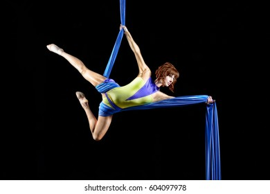 Beautiful young, athletic sexy woman professional aerial circus artist with redhead in yellow costume posing diagonal in the air, light in the darkness. Dancing in the air with balance.
