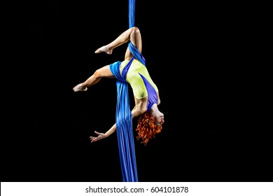 Beautiful young, athletic sexy woman professional aerial circus artist with redhead in yellow costume make coup in the air, light in the darkness. Dancing in the air with balance.