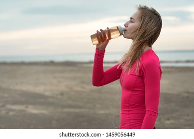 beautiful young athletic woman drinking water from a bottle after training on the beach. Rest after exercises on the sea coast