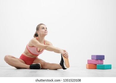 Beautiful young athletic woman in sneakers and red sportswear doing stretching on the floor. Multi-colored blocks for stretching and yoga. The concept of a healthy lifestyle, fitness and sports.