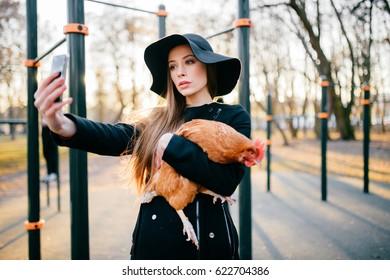 c3fbd929876 Beautiful young attractive brunette model girl with long hair in black coat  and elegant hat making