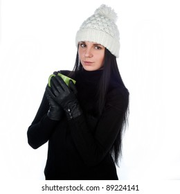 a beautiful young attractive charming girl in a black jacket and white cap with green drinks coffee mugs, isolated over white