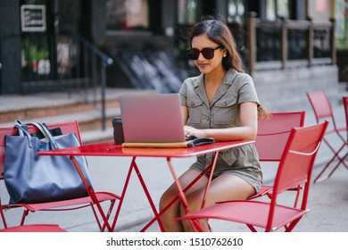 A beautiful, young, attractive and confident Indian Asian woman in a casual outfit and sunglasses smiles as she sits and works on her laptop in a stylish cafe on a street during a summer day.