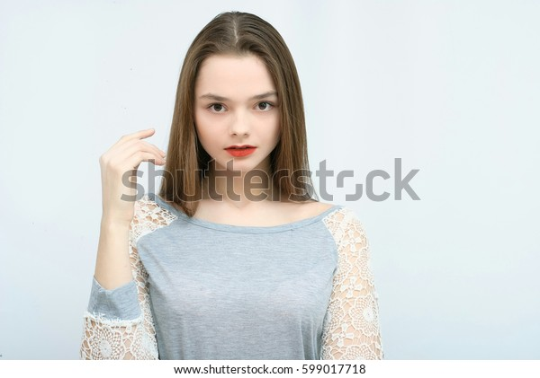 Beautiful young attractive girl in gray t-shirt and blue Jeans posing in studio isolated on white background