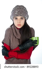 a beautiful young attractive girl in a nice warm gray jacket and a gray knit cap, holding a mug of green, isolated over white