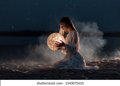 Beautiful young attractive girl on a night beach with sand and stars holds the moon in her hands