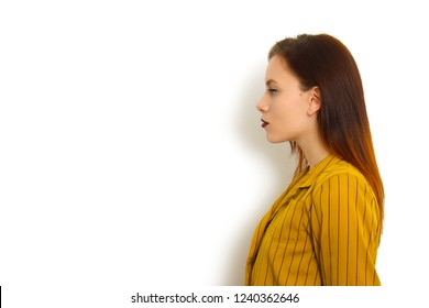 Beautiful young attractive woman standing in front of white background and looking on side of frame with lot of copy-space for your text