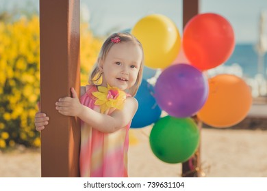 Beautiful young baby blond girl with sensual huge brown eyes posing on sandy beach with yellow flower bush and plenty balloons wearing colourful couturer dress and pink pants.