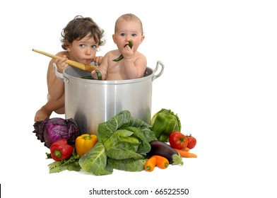 Beautiful young baby in a pan and boy cooking