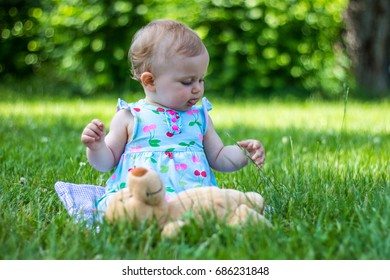 Beautiful young baby sitting on grass in park and playing with favorite toy.