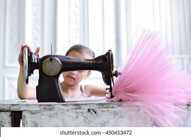 beautiful young ballerina hands on retro sewing machine & pink tutu happy smiling on the background of vintage white wooden interior. tailor manufactore for Party Dancewear Pettiskirt Costume
