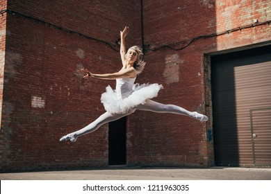 beautiful young ballerina jumping and dancing on urban street