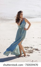 Beautiful young barefoot woman on white sand beach with wind blowing hair and dress. Woman relaxing on the beach