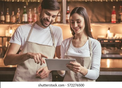 Beautiful young baristas are using a digital tablet and smiling while standing near the bar counter in cafe