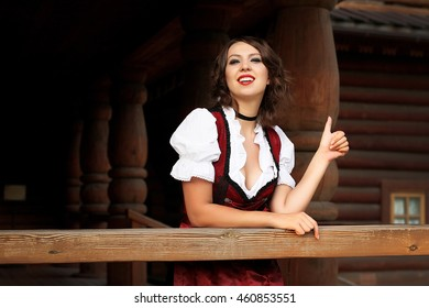 Beautiful, young, bavarian woman in dirndl in wood house
