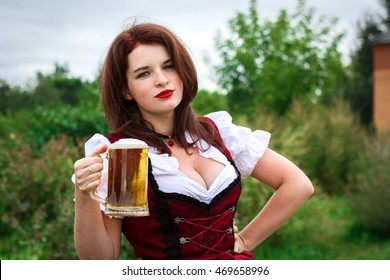 Beautiful, young, Bavarian woman in dirndl holding beer glass