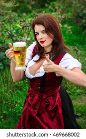 Beautiful, young, Bavarian woman in dirndl holding oktoberfest beer with germany flag.. Close-up