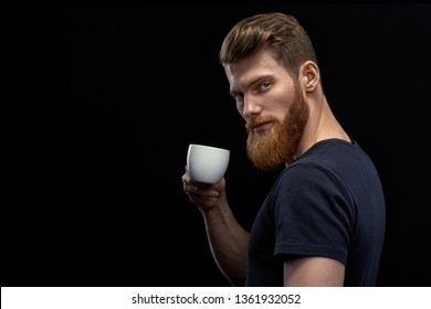 Beautiful young bearded man drinking coffee and looking at camera Resting handsome perfect hairstyle man drinking espresso coffee. Man holding cup of coffee in hand over black background.