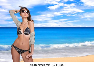 beautiful young bikini model with sea on background