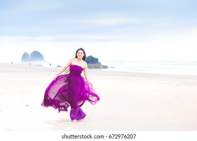Beautiful young biracial teenage girl or young woman standing posing on beach wearing purple or magenta dress blowing in the wind