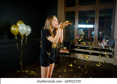 Beautiful young birthday girl after the end of a party. Girl blows off gold confetti from palms. She one in a make-up room. Flowers, balloons, gifts remind of a holiday.
