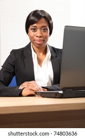 Beautiful young black black business woman working in office sitting to her desk using her laptop, with a serious expression on face. Picture taken from low angle looking upwards.