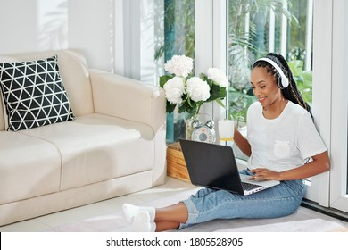 Beautiful young Black female university student sitting on the floor, drinking coffee and doing project on laptop