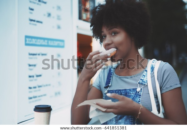 Beautiful young black girl with curly afro hair in jeans overalls is eating pink donut and drinking coffee while standing near street food kiosk on summer evening and thoughtfully looking aside