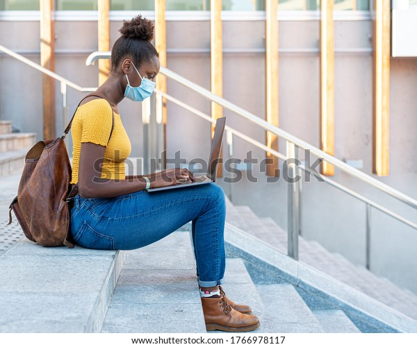 beautiful and young black girl who studies and works with a laptop with surgical mask ,blogger and smart worker in times of epidemic surf the internet, using multimedia content and devices