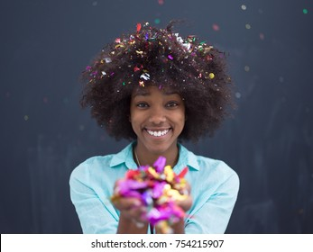 beautiful young black woman celebrating new year and chrismas party while blowing confetti decorations to camera isolated over gray background