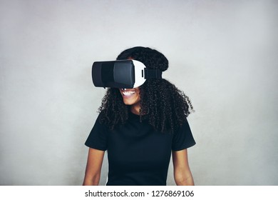 A beautiful young black woman with curly afro hair wears virtual reality VR headset and plays videogames while smiling in studio with grey background