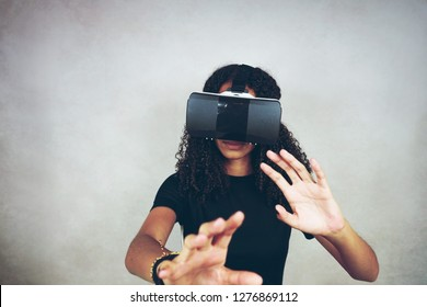 A beautiful young black woman with curly afro hair wears virtual reality VR headset and plays videogames in studio with grey background