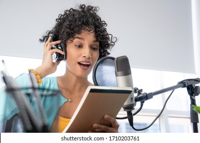 A Beautiful Young Black Woman With Curly Hair Reading Her Notes Script While Doing Her Podcast Show