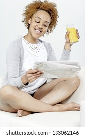 Beautiful young black woman enjoying a newspaper and a glass of juice