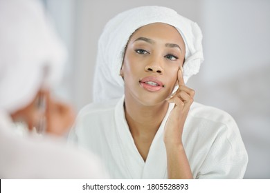 Beautiful young Black woman looking at mirror and checking undereye wrinkles after morning shower