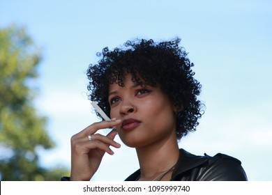 A beautiful young black woman stands outside holding a cigarette.