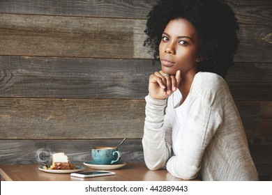 Beautiful young black woman waiting for her friends at a cafe, drinking coffee, with wistful, reflective look, against wooden wall background with copy space for your text or advertising content