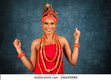 beautiful young black woman wearing edo bridal attire feeling excited and happy and celebrating