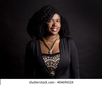 beautiful young black woman is wearing dark dress on grey background