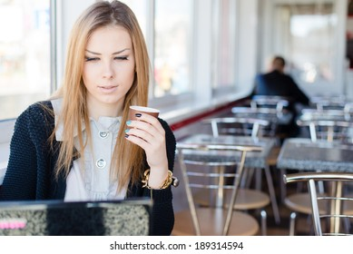 beautiful young blond business woman sitting in a coffee shop drinking coffee and working on laptop computer pc portrait