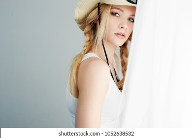 Beautiful Young Blond Country Woman. Cowgirl in Hat near the window