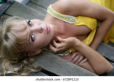 Beautiful young blond female model in glamorous yellow cocktail party dress in the park