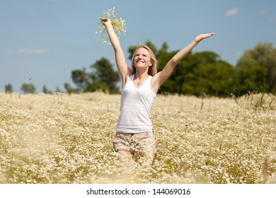 A beautiful young blond girl in a field with white daisies